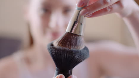 Young-Woman-Using-Brush-And-Powder-While-Doing-Make-Up-1