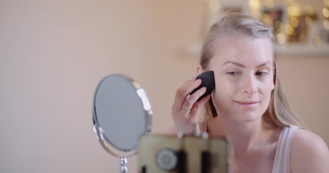 Young-Woman-Doing-Makeup-In-Front-Of-Mirror-At-Home