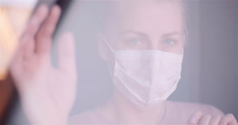 Close-Up-Portrait-Of-Woman-Wearing-Mask-Seen-Through-Window-During-Coronavirus-Outbreak
