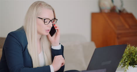 Young-Businesswoman-Talking-On-Mobile-Phone-Using-Laptop-Computer