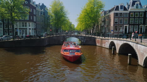 Red-Boat-With-Tourists-On-Canal-In-Amsterdam