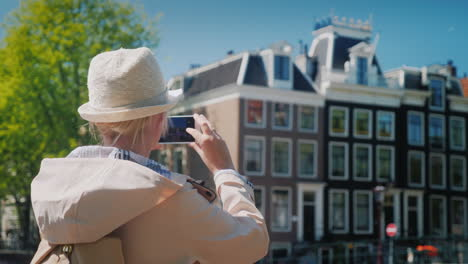 Woman-Takes-Pictures-Of-Buildings-In-Amsterdam