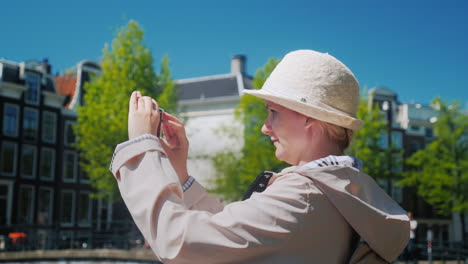 A-Middle-Aged-Woman-Takes-Pictures-Of-Amsterdam