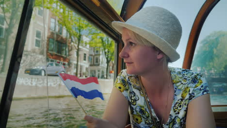Tourist-With-Dutch-Flag-on-Boat-in-Amsterdam