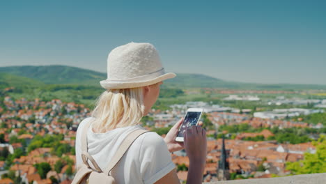 Tourist-With-Smartphone-Above-German-Town