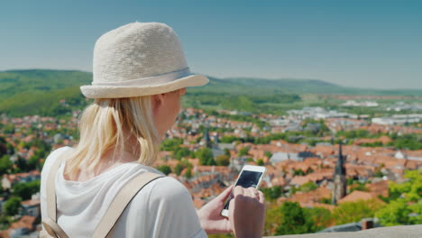 Tourist-With-Smartphone-in-Front-of-German-Town
