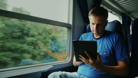 Man-Uses-Tablet-on-a-Train