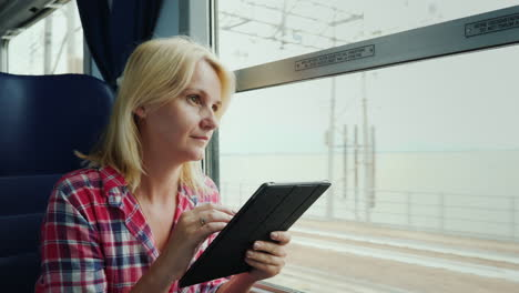 Woman-By-Train-Window-Using-a-Tablet