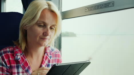 Woman-Using-a-Tablet-by-Tain-Window