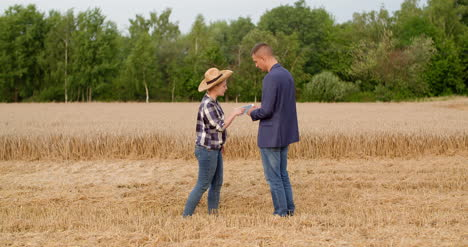 Agriculture-Female-And-Male-Farmers-Talking-At-Wheat-Field-During-Harvesting
