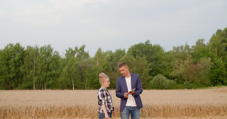 Young-Farmers-Discussing-At-Wheat-Field