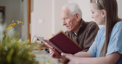 Young-Woman-Surfing-Internet-With-Grandfather-On-Digital-Tablet-1
