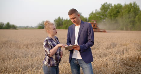 Farmer-Examining-Wheat-Crops-In-Hands-While-Using-Digital-Tablet