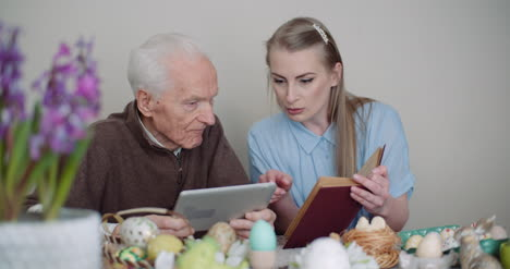 Young-Woman-Surfing-Internet-With-Grandfather-On-Digital-Tablet-3