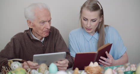 Young-Woman-Surfing-Internet-With-Grandfather-On-Digital-Tablet-5
