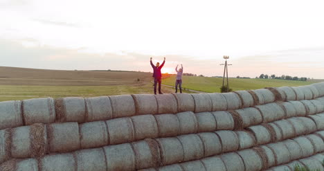 Agriculture-Successful-Farmers-Standing-On-The-Top-Of-A-Bale-Of-Straw