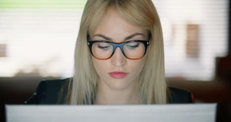Serious-Young-Woman-Using-Computer-Late-At-Work-