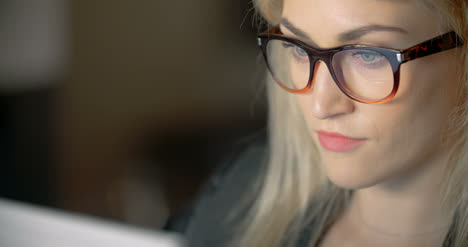 Businesswoman-Wearing-Eyeglasses-While-Using-Laptop-In-Office