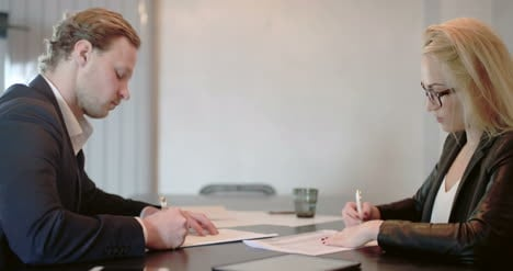 Businesswoman-Signing-Documents-With-Client-In-The-Office