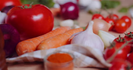Close-Up-Of-Various-Vegetables-On-Table-Rotating-Fresh-Tomato-Carrot-Red-Onion-And-Garlic-