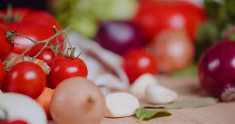 Close-Up-Of-Various-Vegetables-On-Table-Rotating-Fresh-Cherry-Tomatos-Carrot-Red-Onion-And-Garlic-