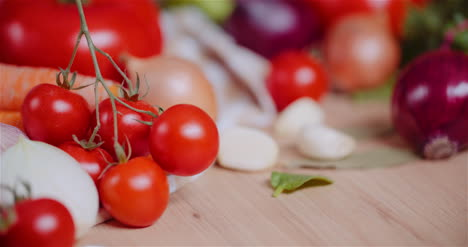 Close-Up-Of-Various-Vegetables-On-Table-Rotating-Fresh-Cherry-Tomatos-Carrot-Red-Onion-And-Garlic-1