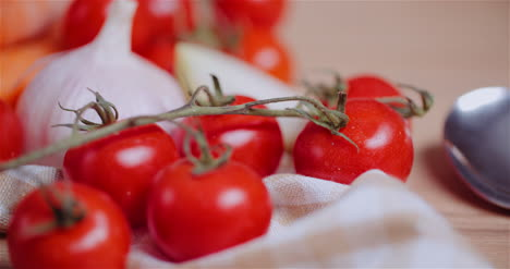 Close-Up-Of-Various-Vegetables-On-Table-Rotating-Fresh-Cherry-Tomatos-Carrot-Red-Onion-And-Garlic-2