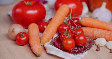 Close-Up-Of-Various-Vegetables-On-Table-Rotating-Fresh-Cherry-Tomatos-Carrot-Red-Onion-And-Garlic-3