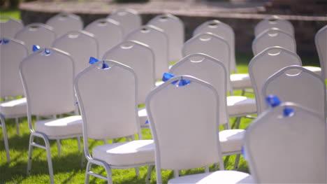 Panning-Shot-Of-Empty-White-Chairs-In-Lawn-At-Wedding-Ceremony