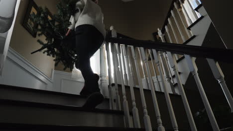 Woman-Carries-Christmas-Tree-Upstairs