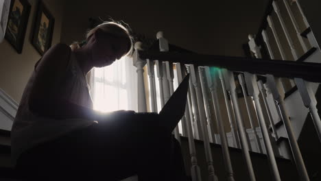 Sunlit-Woman-Uses-Tablet-on-Stairs
