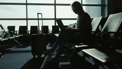 Business-Woman-With-Laptop-In-Airport-Terminal