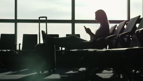 Woman-In-Airport-Uses-A-Smartphone