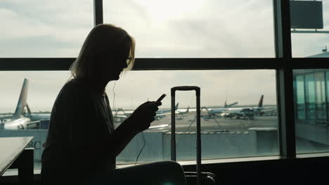 Woman-With-Suitcase-Uses-Phone-in-Airport