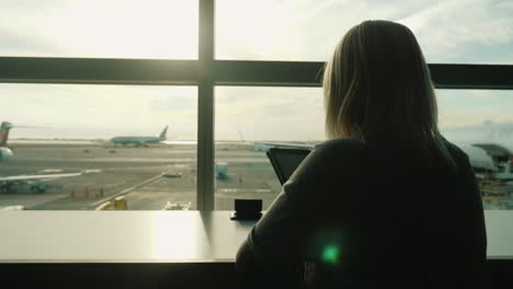 Woman-Using-Tablet-by-Airport-Terminal-Window