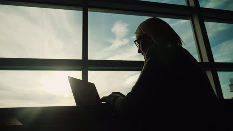 Business-Woman-Working-by-Large-Window