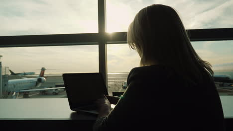 Woman-With-Laptop-Sits-Airport-Window