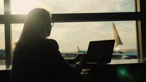 Woman-With-Laptop-Daydreaming-in-Airport