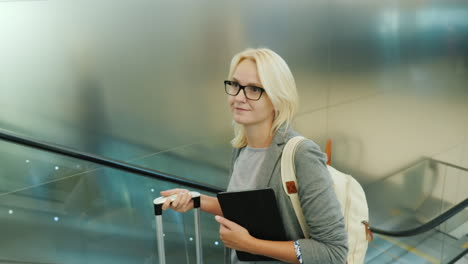 Woman-on-Escalator-with-Tablet-and-Suitcase