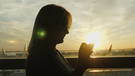 Woman-Using-Smartphone-In-Airport-At-Sunset