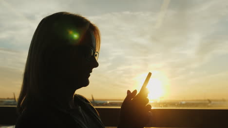 Woman-Uses-Smartphone-In-Airport-At-Sunset
