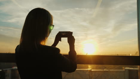 Woman-Takes-Pictures-Of-An-Airfield-At-Sunset