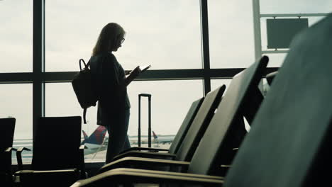 Woman-in-Airport-Uses-a-Tablet