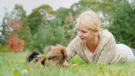 Woman-Playing-With-Puppies-on-a-Lawn