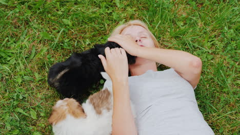 Woman-Playing-With-Puppies-on-Lawn