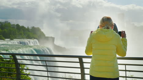 Woman-Looks-At-Niagara-Falls-Through-Binoculars