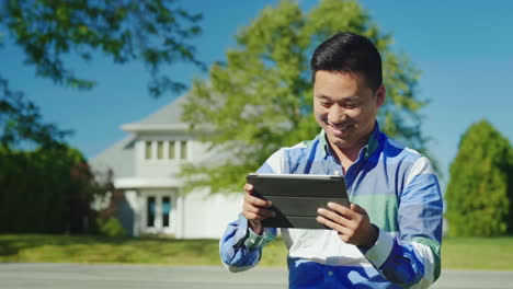 Happy-Man-Uses-a-Tablet-Near-Home