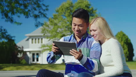 Couple-Use-Tablet-by-Suburban-Home