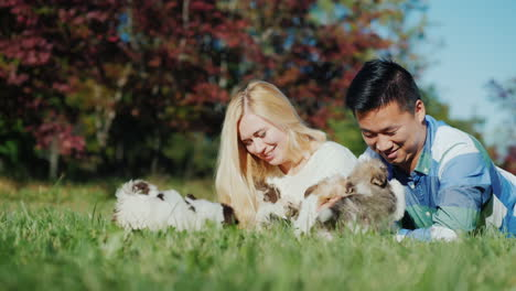 Couple-Playing-With-Puppies