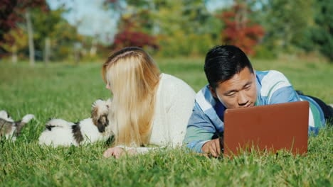 Young-Couple-With-Puppies-and-Laptop